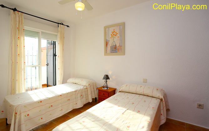 dormitorio con 2 camas individuales y balcón