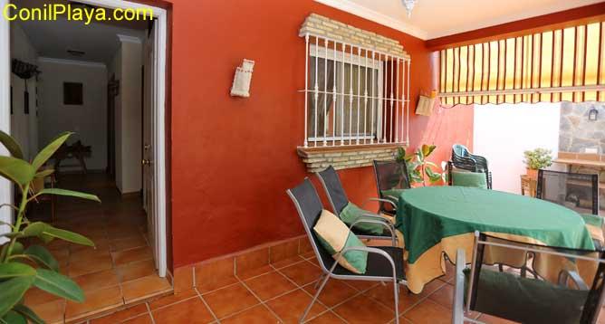 porche con mesa y sillas e interior de la casa