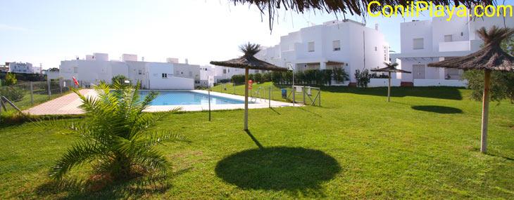 La piscina está el jardín y está rodeada de césped.