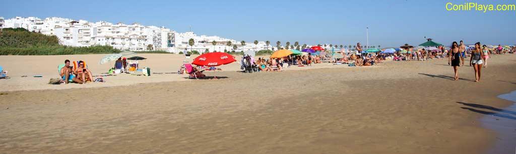 playa de los bateles con conil al fondo y gente paseando por la playa