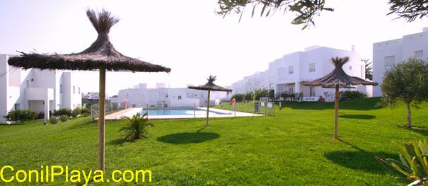 La piscina está rodeada de amplios jardínes con césped y sombrillas.