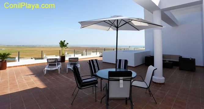 terraza muy amplia con mesas, sillas y tumbonas
