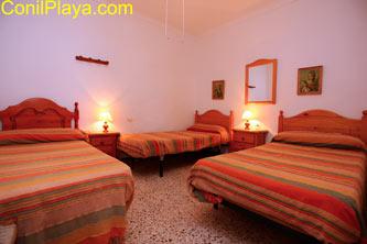 Dormitorio con tres camas individuales y ventilador de techo.