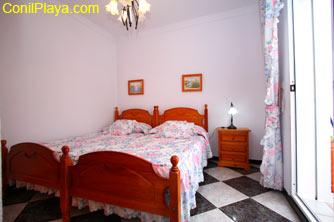 Dormitorio de dos camas individuales con puerta de salida a patio interior privado.
