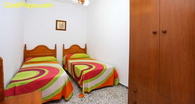 Dormitorio con dos camas individuales y terraza.