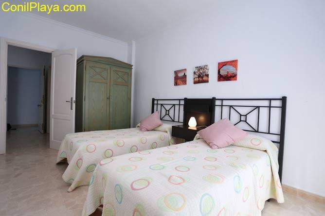 Dormitorio con 2 camas individuales y armario.