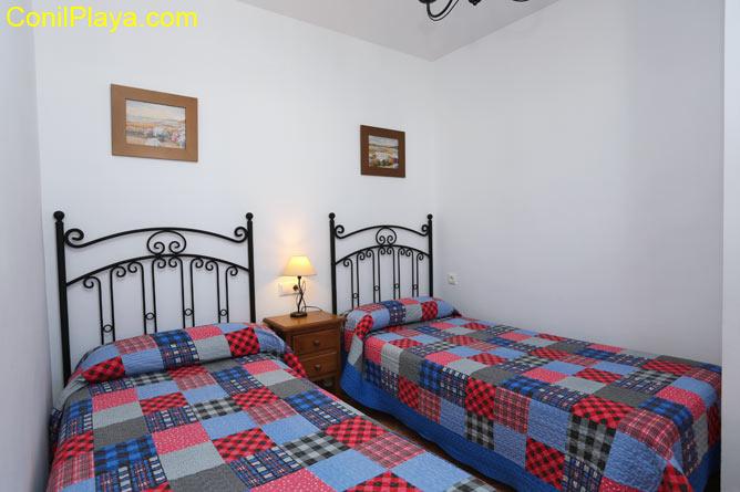Dormitorio con armario empotrado y dos camas individuales.