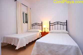 Dormitorio de dos camas individuales con armario empotrado y ventana al patio interior.