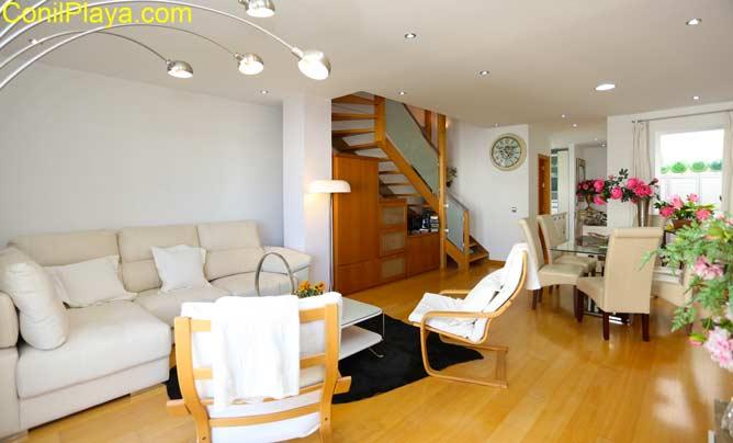 salón con sofá y mesa comedor con sillas. Al fondo las escaleras