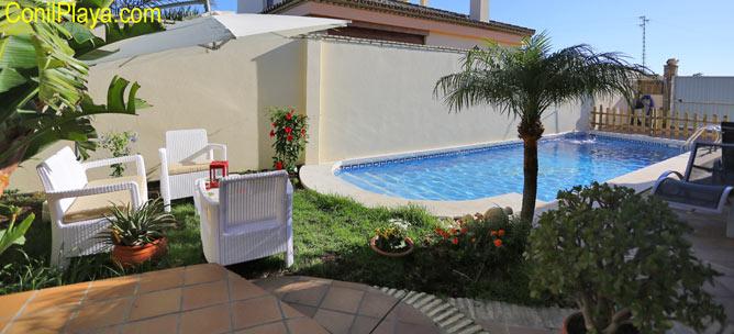 Sombrilla, mesa y sillas de la piscina