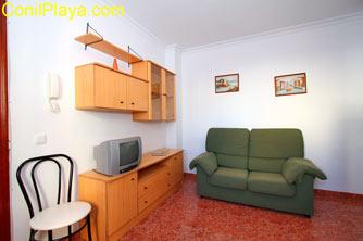 Salón con sofá y mueble con televisión.
