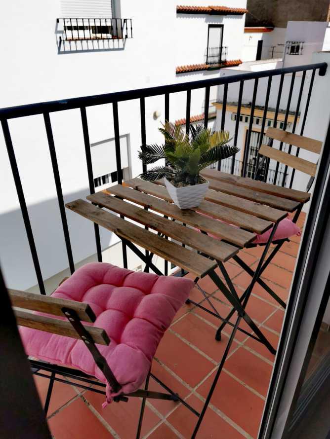 terraza del apartamento con mesa y 2 sillas