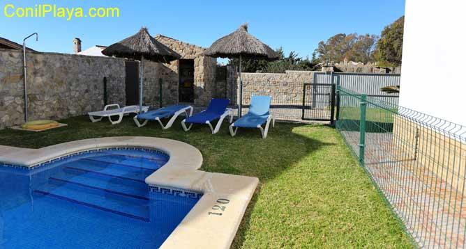 piscina vallada con tumbonas y 2 sombrillas y ducha
