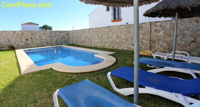 piscina privada con tumbonas y sombrillas