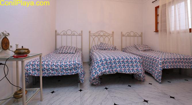 Habitación con tres camas.