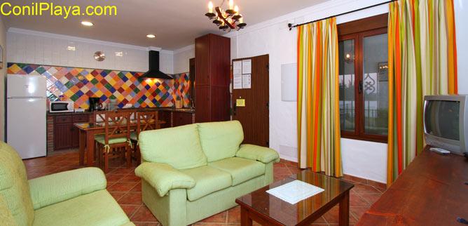 El salón de la casa con el sofá, el comedor y al fondo la cocina.