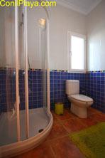 El cuarto de baño cuenta con una amplia ducha con mampara.