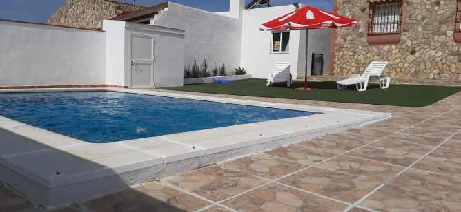 piscina con tumbonas y sombrilla