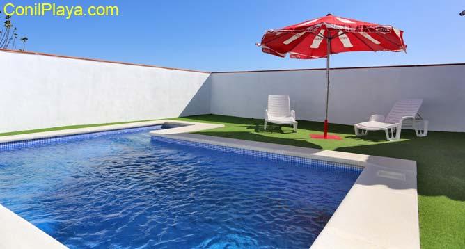 piscina con 2 tumbonas y sombrilla