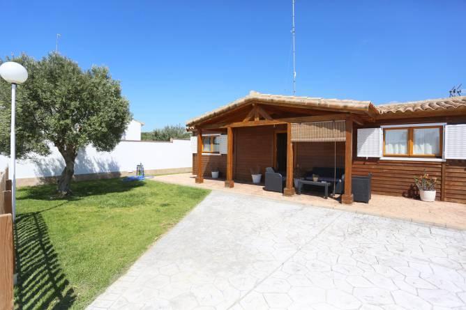 Vista general del jardín, el porche, la casa y la piscina.