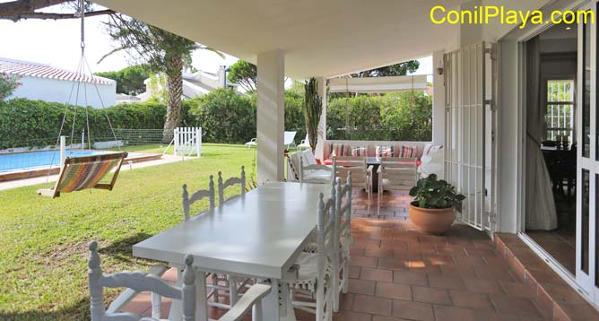 mesa y sofá del porche al fondo