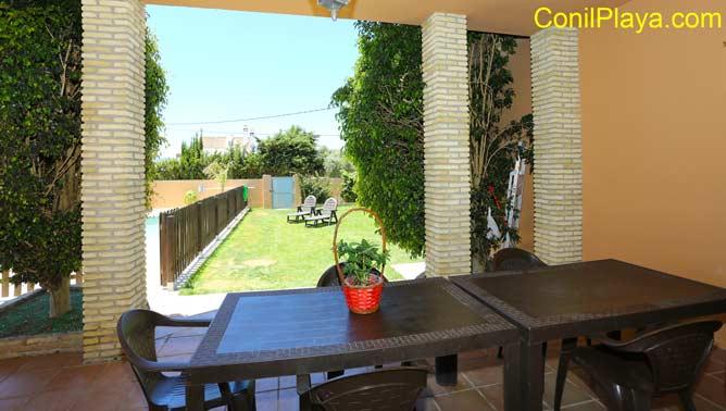 amplio porche junto a la piscina y al jardín.