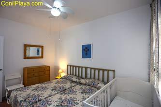 dormitorio con 2 camas y cuna