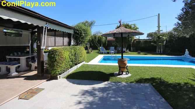 mesa con sombrilla en la piscina y en el porche