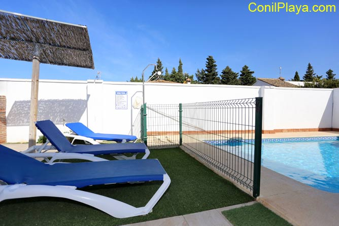 Vista general del jardin con la piscina y la barbacoa.