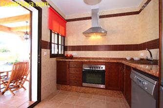 La cocina se encuentra junto al porche, ideal para cenar en las noches de Conil
