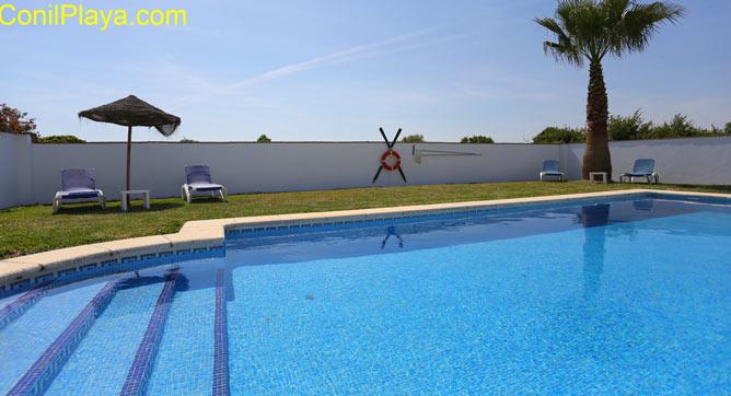 La piscina es amplia y tiene mucho césped.