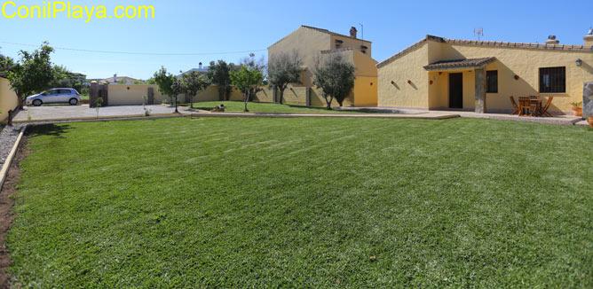 La casa tiene porche y frente a él hay una gran extensión de jardin.