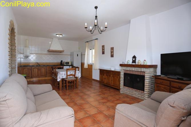 Vista general del salón con chimenea y la cocina al fondo.