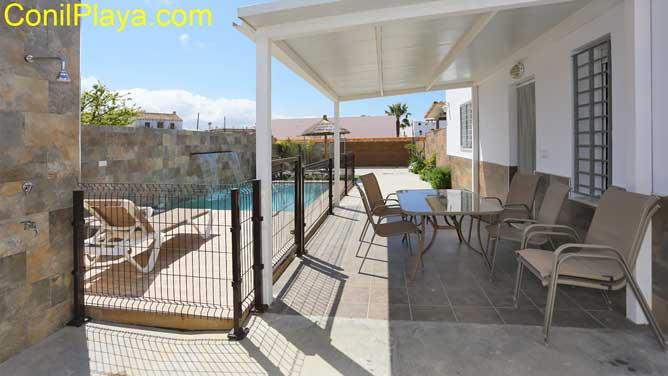porche con mesa y sillas y vistas a la piscina