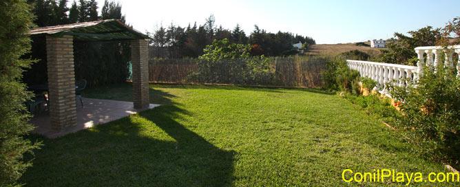El jardín es amplio y con césped.
