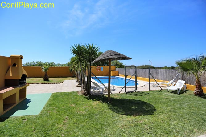 jardín con césped y la piscina al fondo