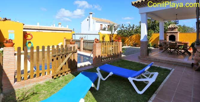 Jardín con césped y tumbonas y al fondo el porche y la barbacoa