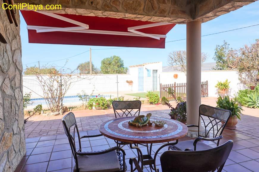 porche con mesa y sillas frente a la piscina