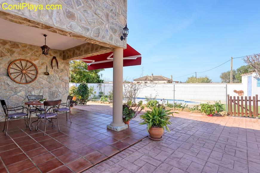 Jardín con césped, piscina y porche