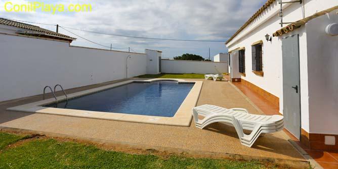 Jardín con césped junto a la piscina