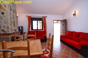 mesa del comedor de madera y al fondo los sofás del salón