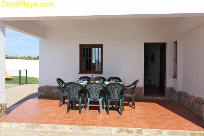 porche con mesa y 8 sillas junto a la piscina