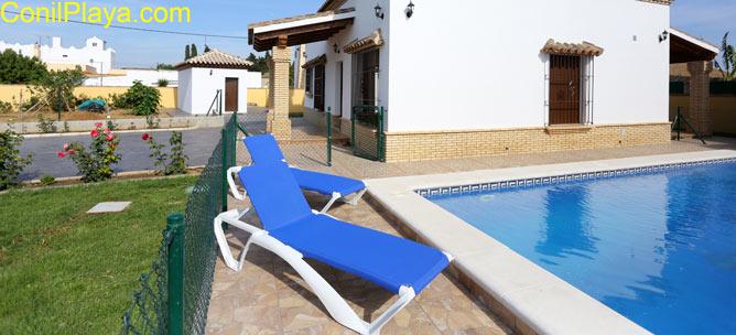 piscina y al fondo el jardín con césped
