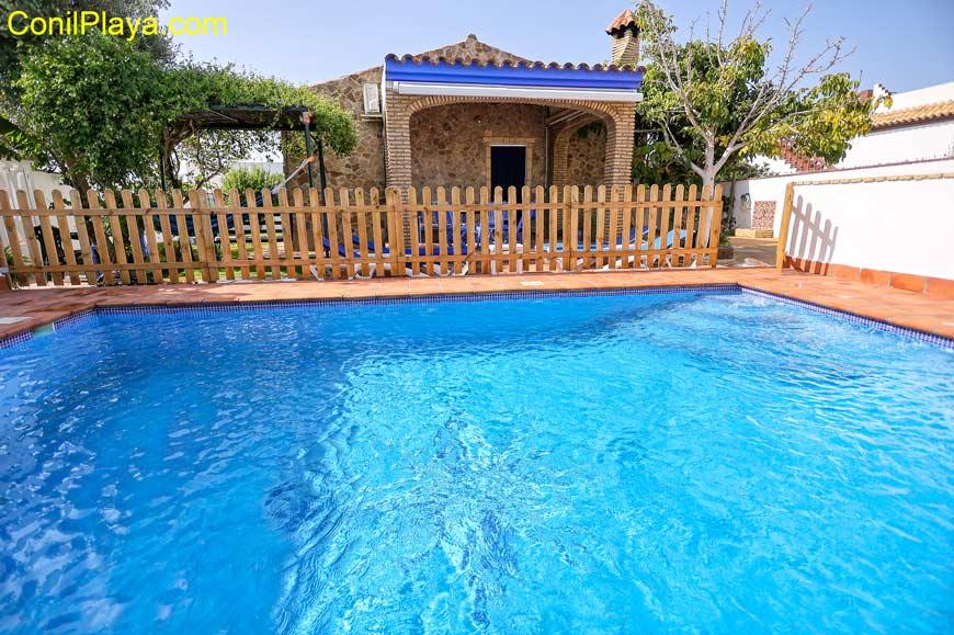 La piscina y al fondo la casa.