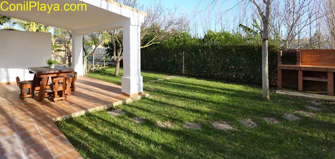 porche y jardín con césped y barbacoa