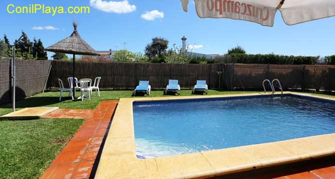 piscina con ducha, sombrillas y tumbonas