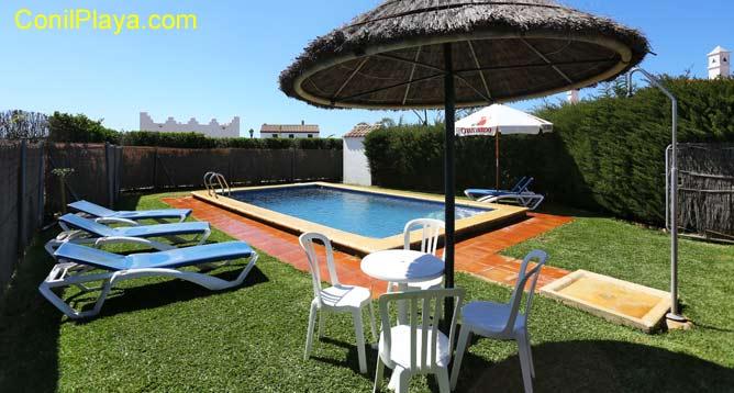 mesa y sillas con la piscina al fondo