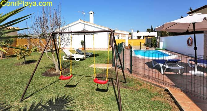 jardín amplio con césped y columpios
