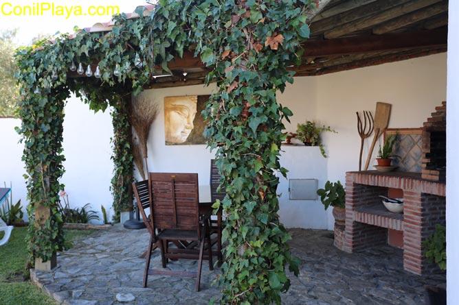 La barbacoa se encuentra en el jardín, debajo de los arboles.