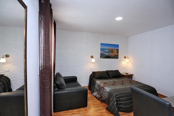 dormitorio con cama de matrimonio y sofá